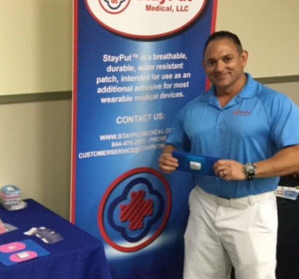 StayPut Medical booth with owner Mike Mangus, demonstrating a StayPut adhesive patch